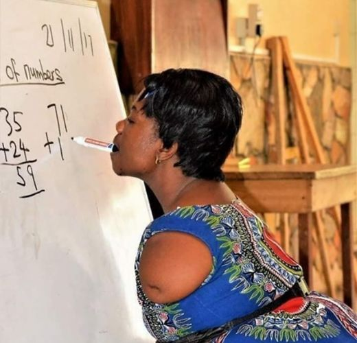 Teacher with no arms uses chalk in mouth to write and teach pupils